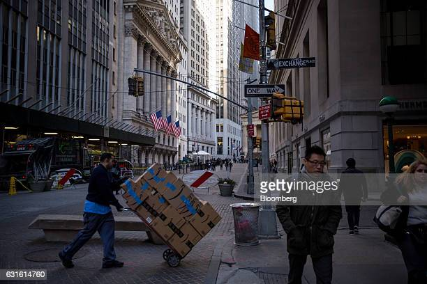 Man pushes a dolly of Amazon.com Inc. Boxes as pedestrians walk along Broad Street near the New York Stock Exchange in New York, U.S., on Friday,...