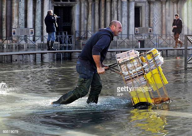 A man pushes a handcart laden with newspapers on the flooded Piazza San Marco on December 01 2009 in Venice Much of the historic Italian city of...