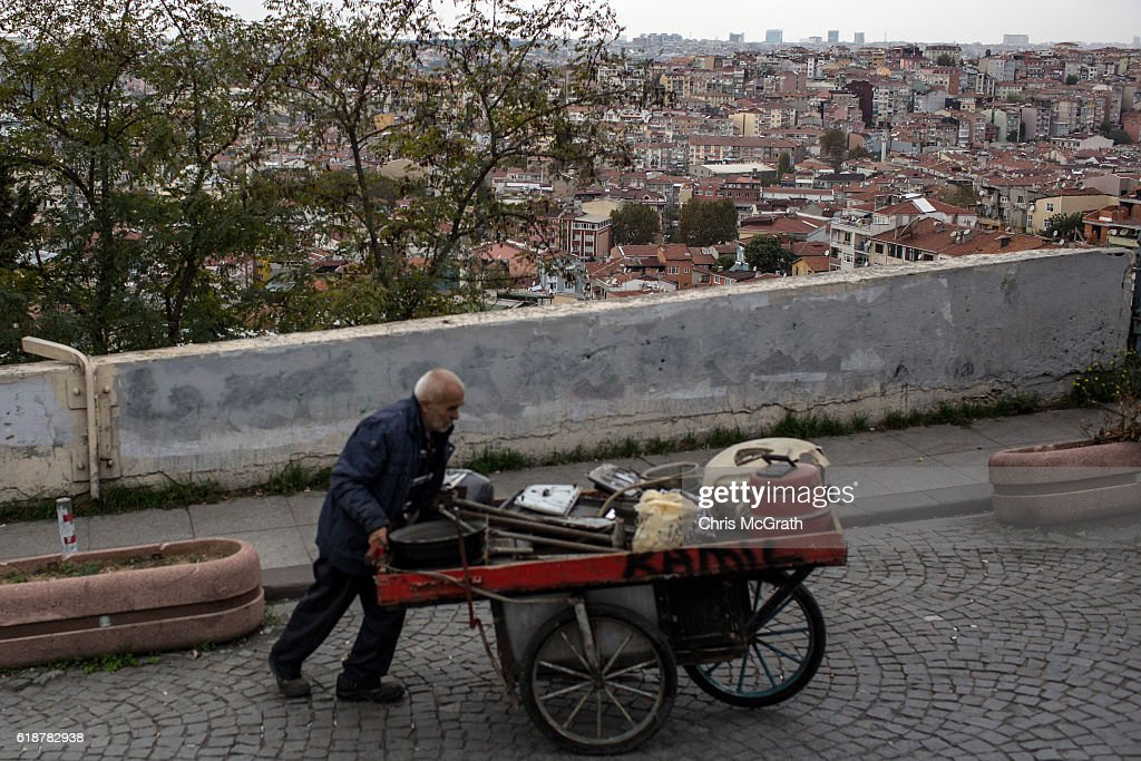 A man pushes a junk cart up a hill in front of a view of the Kasimpasa neighbourhood on October 27, 2016 in Istanbul, Turkey. Turkey's President Recep Tayyip Erdogan was born in the Kasimpasa neighbourhood before returning to his families home town of Rize. Since the failed coup attempt on July 15, 2016 which saw 240 people killed including 173 civilians, Turkish authorities initiated a state of emergency, leading to an unprecedented crackdown on individuals and organizations with links to US-based cleric Fethullah Gulen and his organization blamed for instigating the uprising. The purge, targeting teachers, journalists, soldiers, judges, academics, police, military leaders, schools and universities has so far seen approximately 100,000 people dismissed, 70,000 detained, 32,000 arrested, 130 media outlets closed and some 15 universities shuttered. The failed coup and subsequent purge only appears to have further bolstered the president's popularity and increased nationalism across the country with July 15th having been marked as a new national holiday. Turkish flags, already prominently displaying all over have increased in numbers, as well as posters of those killed fighting the coup plotters appearing in train stations and public squares. The Bosphorus Bridge in Istanbul, which saw heavy fighting during the coup has been renamed the '15th July Martyr's Bridge'. These changes, follow a year of instability in the country with constant terrorist attacks, an economic downturn, plummeting tourism, and a refugee crisis, all contributing to Turkish society undergoing its most dramatic restructuring in decades.