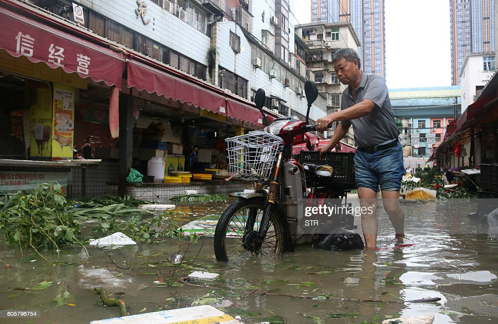 TOPSHOT - A man pushes a motorbike through a flooded street in Xiamen, in China's eastern Fujian province after Typhoon Meranti made landfall on September 15, 2016. Typhoon Meranti made landfall in Fujian early on September 15, with winds up to 230kph, knocking out electricity in some areas and causing rail delays. / AFP / STR / China OUT