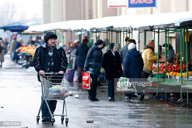 A man pushes a shopping cart loaded with bags past stalls selling fresh fruit and vegetables outside the city's central market in Riga Latvia on...