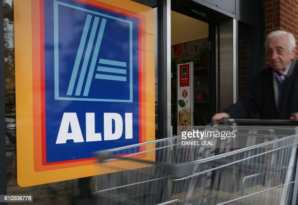 A man pushes a shoppping trolley as he arrives at an Aldi supermarket store in London on September 26 2016 Aldi UK announced on Monday that it will...