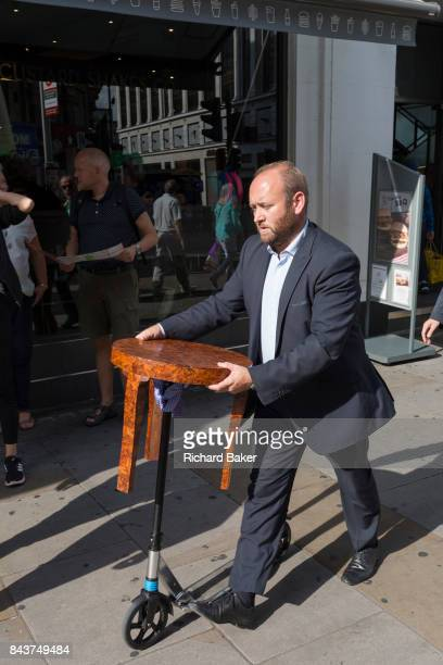 A man pushes a small scooter that supports a wooden threelegged table on 1st September 2017 in London England