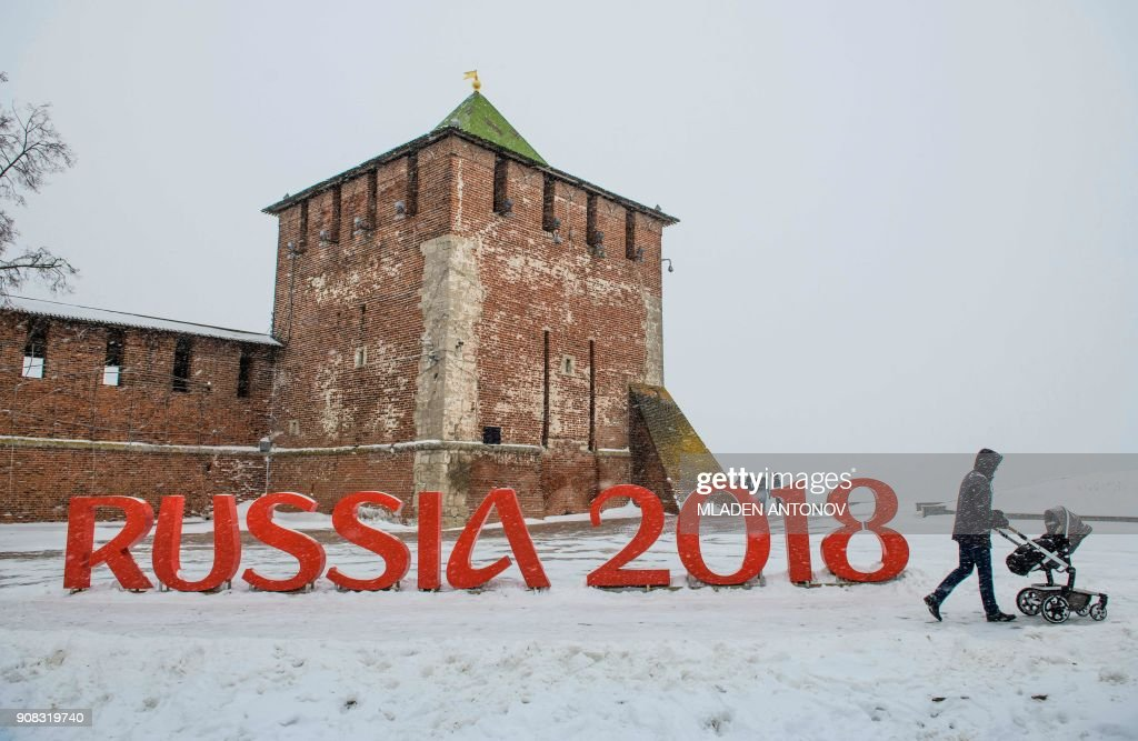 TOPSHOT - A man pushes a stroler past a FIFA World Cup 2018 emblem placed in front of the Nizhny Novgorod's Kremlin on January 21, 2018. / AFP PHOTO / Mladen ANTONOV