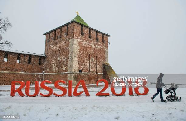 TOPSHOT A man pushes a stroler past a FIFA World Cup 2018 emblem placed in front of the Nizhny Novgorod's Kremlin on January 21 2018 / AFP PHOTO /...