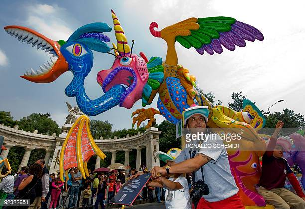 A man pushes a traditional 'Alebrije' during the third parade of 'The Night of the Alebrijes' at Madero street in Mexico City on October 24 2009 The...