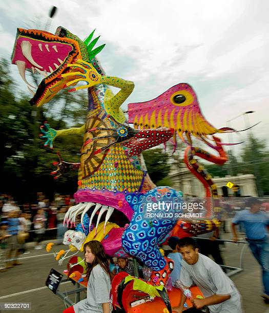 A man pushes a traditional 'Alebrije' during the third parade of The Night of the Alebrijes at Madero street in Mexico City on October 24 2009 The...
