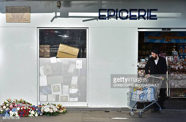 TOPSHOT A man pushes a trolley as he walks out of the Hyper Cacher supermarket following a ceremony marking the second anniversary of the deadly...