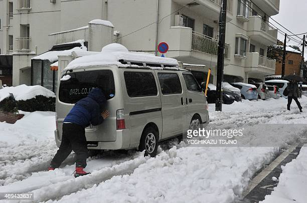 A man pushes a vehicle after it lost traction and skidded on a snow covered road in Tokyo on February 15 2014 as trafic is disrupted after a heavy...