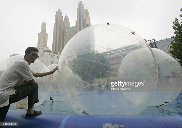 A man pushes a water walking ball at a square on August 13 2006 in downtown Tianjin Municipality a megacity neighbouring Beijing China The...