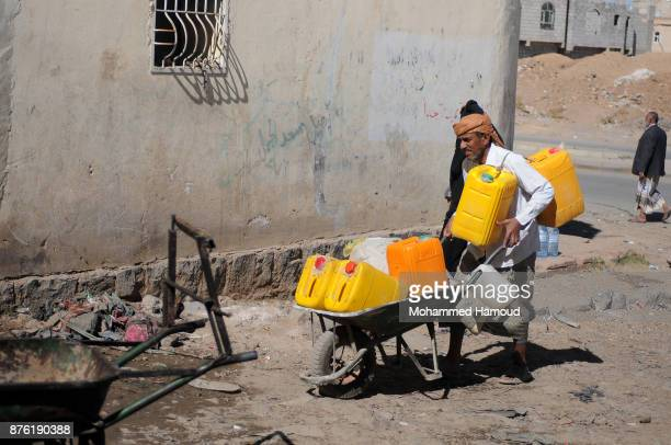 A man pushes a wheelbarrow carrying jerry cans to be filled with clean water from a charity water pipe on November 18 2017 in Sana'a Yemen The...