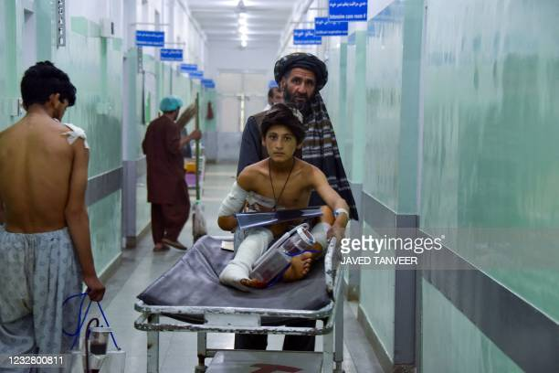 Man pushes an injured boy on a stretcher along a hospital corridor in Kandahar on May 10 as he receives medical treatment after being hurt by a...