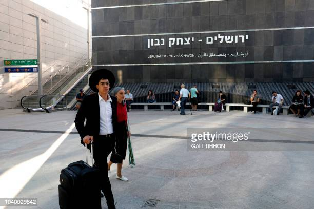A man pushes his bags at the Jerusalem station on September 25 as he prepares to board the new highspeed train Israelis climbed aboard the country's...
