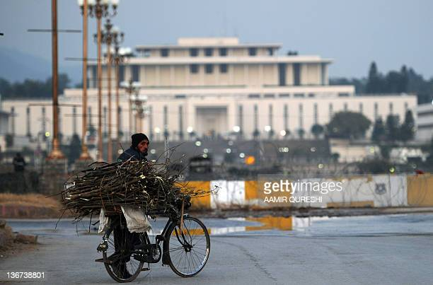 A man pushes his bicycle carrying fire wooden in front of the Presidential Palace in Islamabad on January 11 2012 Pakistan's army warned on January...