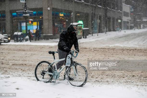A man pushes his bicycle during a winter storm in New York on January 4 2018 A giant winter bomb cyclone walloped the US East Coast on Thursday with...