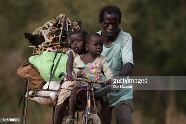 A man pushes his bike carrying his two children up a hill after crossing a small wooden bridge over a river from South Sudan into Uganda on February...