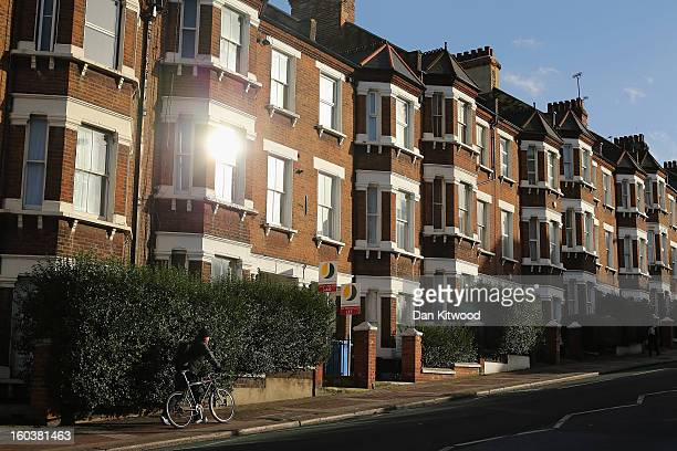 A man pushes his bike past a row of houses near Battersea on January 30 2013 in London England According to a report from independent analysts Oxford...