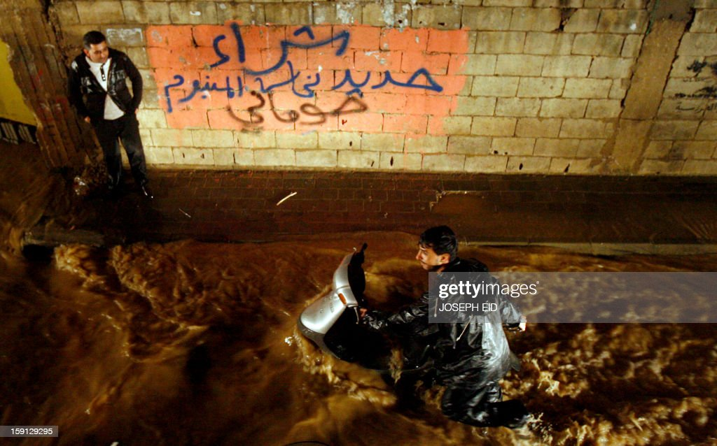 A man pushes his moped through flood waters in southern Beirut, on January 8, 2013 as stormy weather, including high winds and heavy rainfall, lashed the eastern Mediterranean coast, downing power lines and trees and causing several injuries in a number of countries.