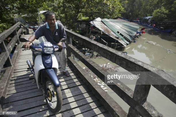 A man pushes his motorcycle over a bridge in the fishing village of Balik Pulau Penang 27 December 2004 The fishing village was the hardesthit area...