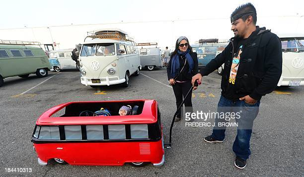 A man pushes his son in a miniature Volkswagen bus at 'Das OCTO Fest 2013' a swap and display gathering for enthusiasts and owners of 1967 and...