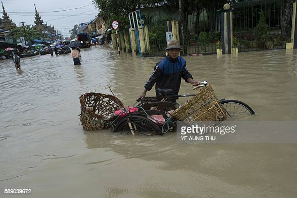 A man pushes his trishaw through the water after seasonal flooding hit the city of Pathein in the Irrawaddy region on August 13 2016 Myanmar's...