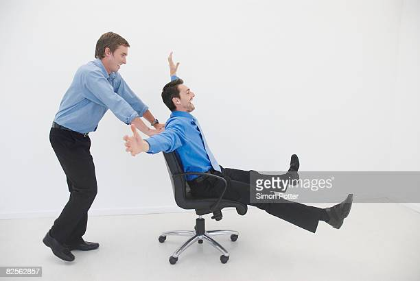 Man pushes man in office chair