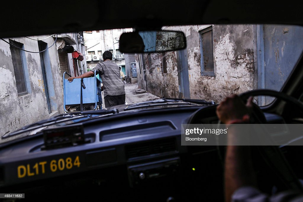A man pushes materials for recycling as taxi driver Gurmeet Singh drives a taxi in New Delhi, India, on Saturday, Sept. 19, 2015. As cabs lured by app-based platforms proliferate in India, where car ownership is low and public transportation services in most cities and towns havent kept pace with the needs of a growing population, drivers are facing stiffer competition for rides. Photographer: Dhiraj Singh/Bloomberg via Getty Images