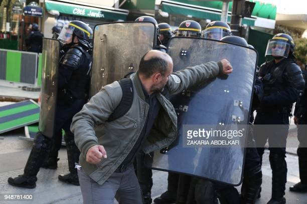 TOPSHOT A man pushes scuffles with CRS antiriot police during a demonstration on April 19 in Paris as part of a multi branch day of protest called by...