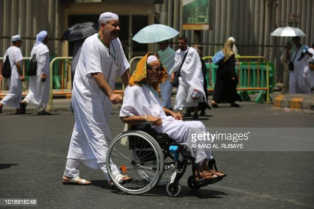 A man pushes the wheelchair of a fellow Muslim pilgrim in a street in Saudi Arabia's holy city of Mecca on August 18 ahead of the start of the annual...