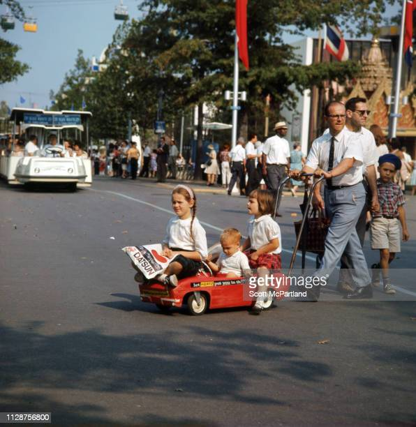 A man pushes three children in a Hertzbranded stroller at the World's Fair in Flushing Meadows Park in Queens New York New York June 1965