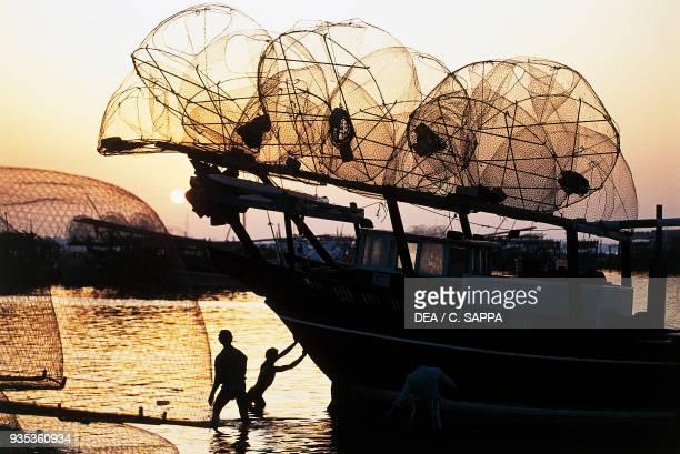 Man pushing a fishing boat with nets out to sea at dusk Doha Qatar
