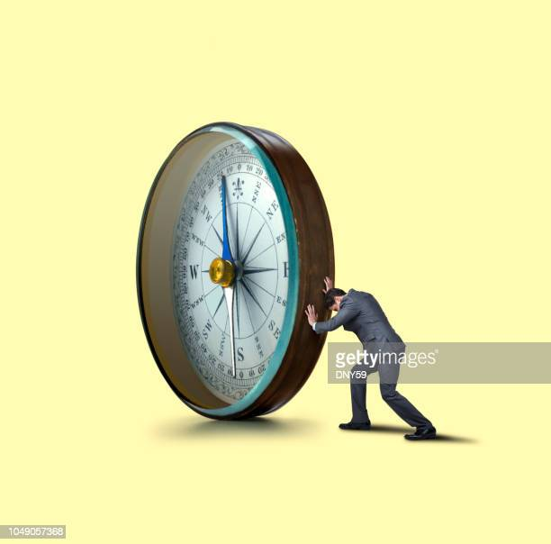 man pushing a large compass - morality stock pictures, royalty-free photos & images