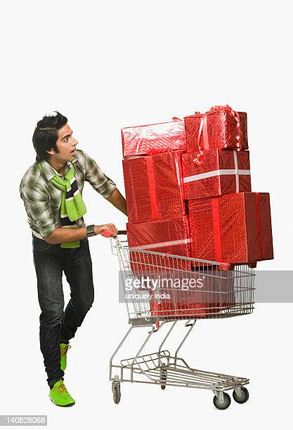 Man pushing a shopping cart filled with gifts and looking surprised