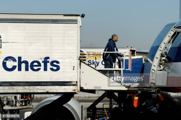 Man pushing a trolley on to an American Airlines Airbus A300600R parked at the terminal with LSG Sky Chefs catering trucks