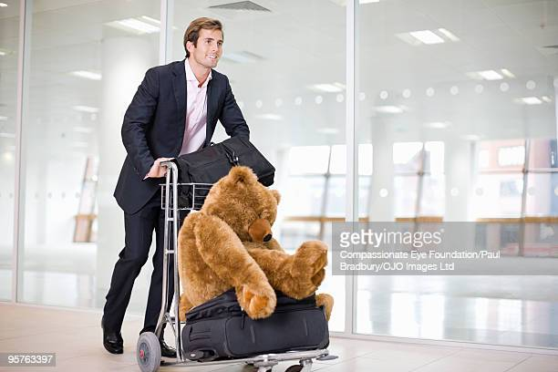 Man pushing airport trolley and stuffed animal