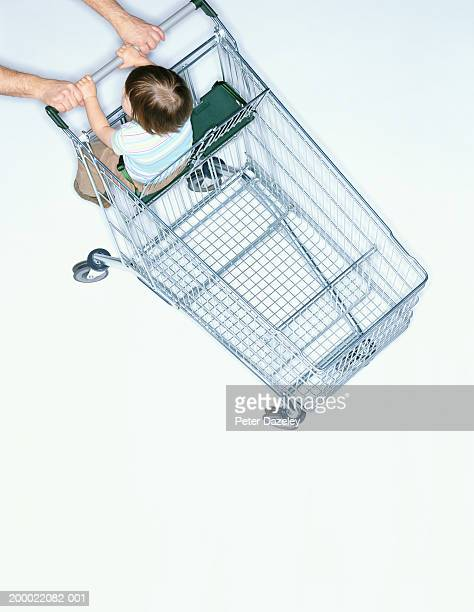 Man pushing baby girl (18-21 months) in shopping cart, elevated view