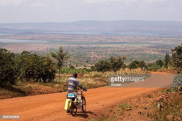 man pushing bicyle on red dirt road in rural rwanda - rwanda stock pictures, royalty-free photos & images