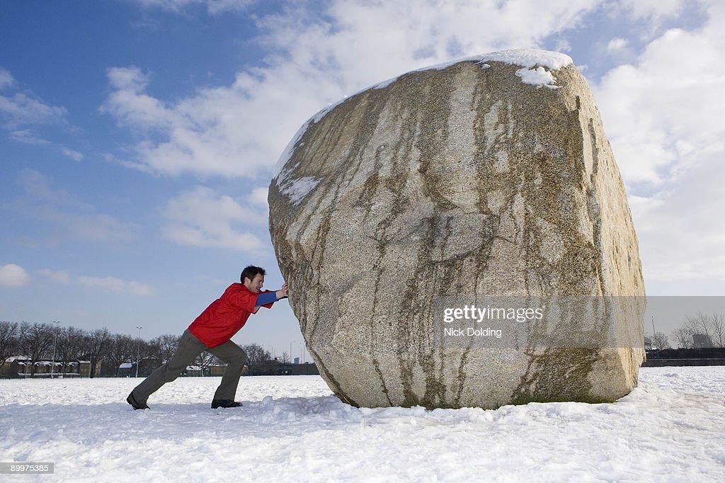 Man pushing boulder : ストックフォト