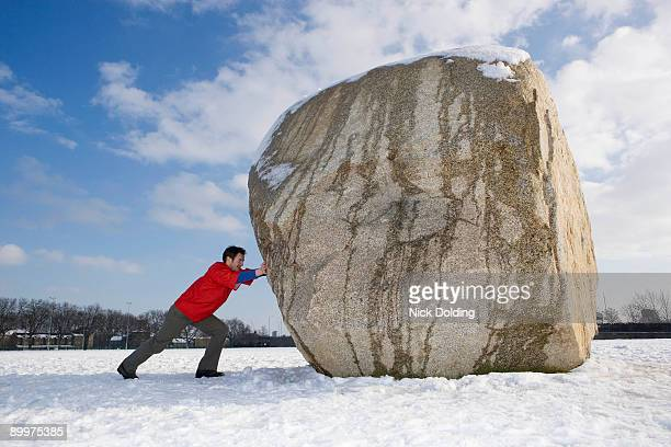 man pushing boulder - kei stockfoto's en -beelden