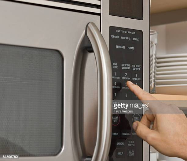Man pushing button on microwave