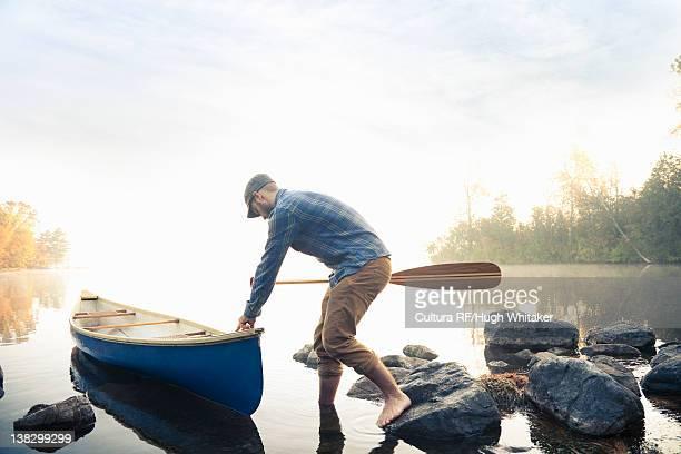 Man pushing canoe into still lake