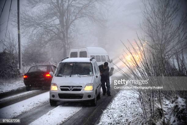 Man pushing car stuck on snowy road UK