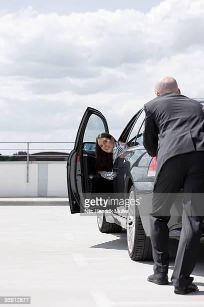 man pushing car woman observing