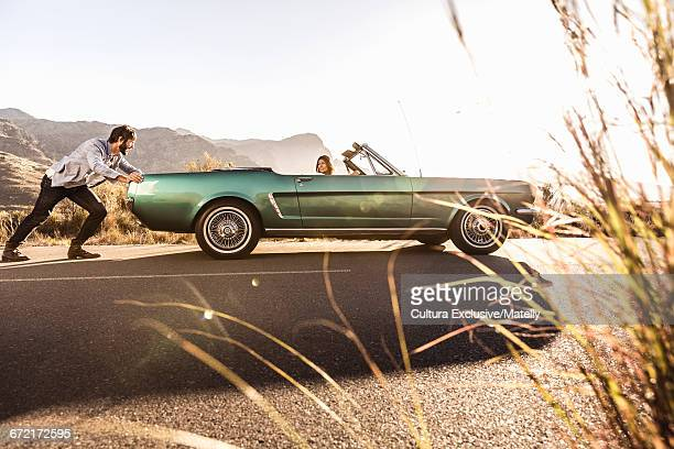 Man pushing convertible car, Franchook, South Africa