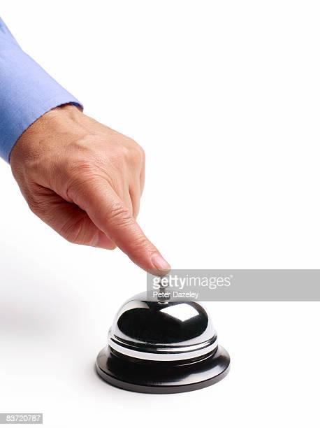 Man pushing desk service bell.