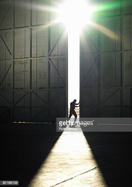 man pushing door open - vastberadenheid stockfoto's en -beelden