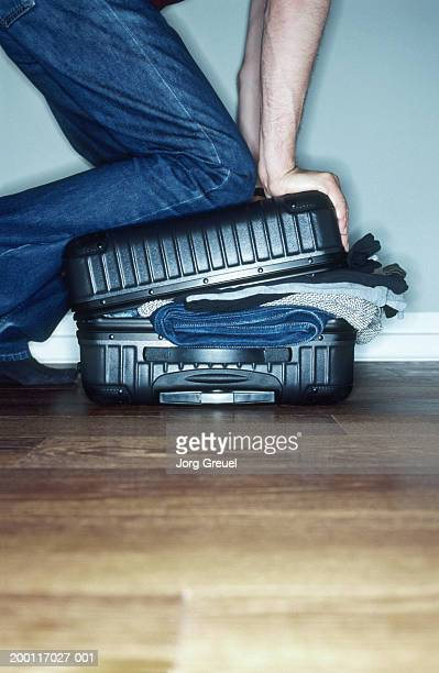 Man pushing down on over filled suitcase, ground view