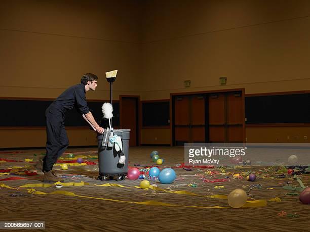 Man pushing dustbin in auditorium