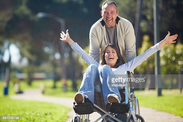 Man pushing enthusiastic woman in wheelchair