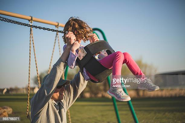 Man pushing girl on swing